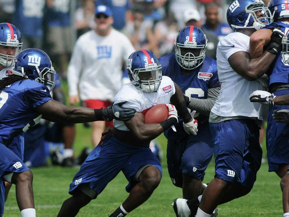 Running back David Wilson carries the ball through a hole during practice at New York Giants training camp at the University at Albany on Sunday, July 29, 2012 in Albany, NY.   (Paul Buckowski / Times Union) Photo: Paul Buckowski
