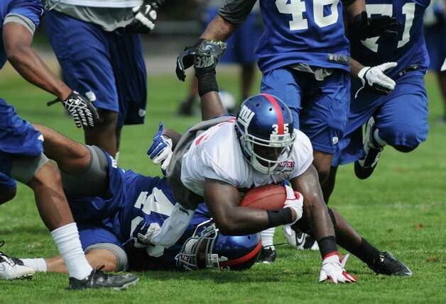 Running back Andre Brown hits the ground after being tripped up during practice at New York Giants training camp at the University at Albany on Sunday, July 29, 2012 in Albany, NY.   (Paul Buckowski / Times Union) Photo: Paul Buckowski