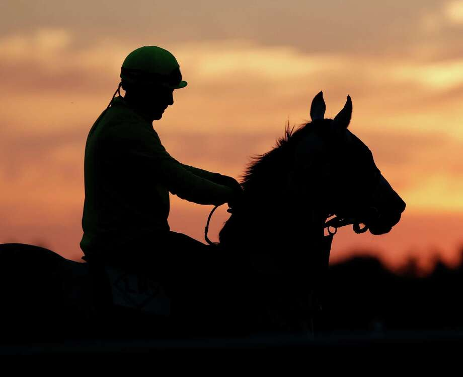 An exercise rider rides a horse during morning workouts at Saratoga Race Course in Saratoga Springs, N.Y., on Thursday, July 19, 2012. The 144th Saratoga horse racing season starts on Friday. (AP Photo/Mike Groll) Photo: Mike Groll / AP
