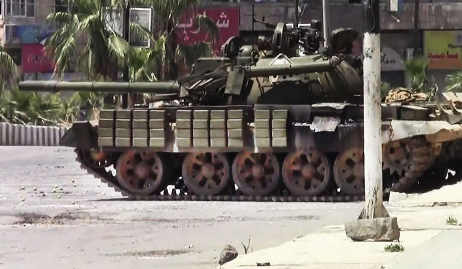 This image made from amateur video released by the Shaam News Network and accessed Sunday, July 29, 2012, shows a Syrian military tank in Daraa, Syria. (AP Photo/Shaam News Network via AP video)