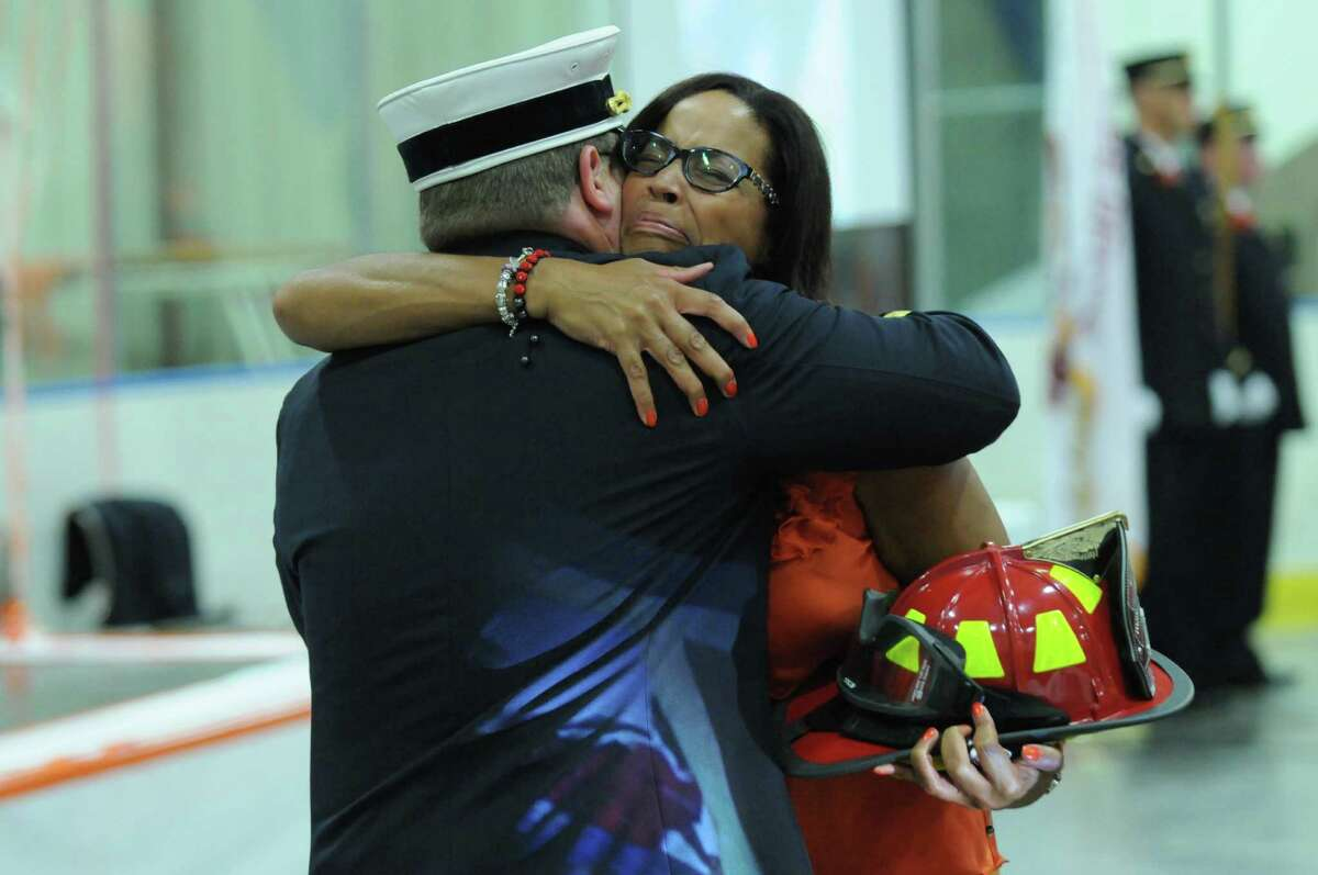 Laurel McAdoo hugs Delmar Fire Chief Dan Ryan after he presented her with the helmet of her son Myles McAdoo, 9, who died this week of pediatric brain cancer, during a celebration of Myles life attended by hundreds of people at the Bethlehem YMCA on Sunday July 29, 2012 in Delmar, NY. Myles was made a member of the department earlier this year. (Philip Kamrass / Times Union)