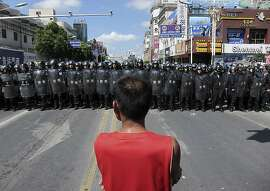 A protester stands in front of lines of riot police officers Saturday, July 28, 2012, in Qidong, Jiangsu Province, China.  Authorities in eastern China dropped plans for a water-discharge project Saturday after thousands of protesters, angry about pollution, took to the streets in the latest of many such confrontations in a country where three decades of rapid economic expansion have come at an environmental price. (AP Photo/Eugene Hoshiko)