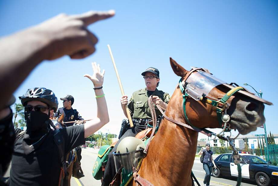 Orange County Police Officers pushes protesters back during a protest to show outrage for the several recent office involved shootings on July 29, 2012 in Anaheim, California. For the past week, protesters have clashed with police resulting in both property damage and many arrests. Photo: Jonathan Gibby, Getty Images