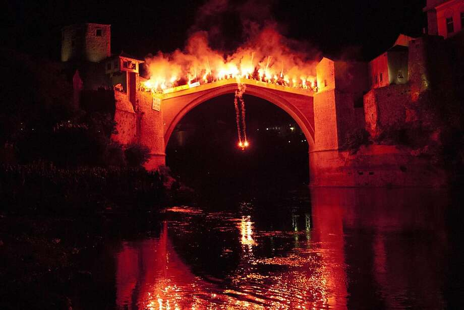 A diver takes a plunge with torches from the 25 meters (82 feet)-high Old Mostar Bridge into the Neretva River during the annual night high diving in Mostar, 140 kilometers (87 miles) south of Bosnian capital of Sarajevo, Sunday, July 29, 2012. Photo: Amel Emric, Associated Press