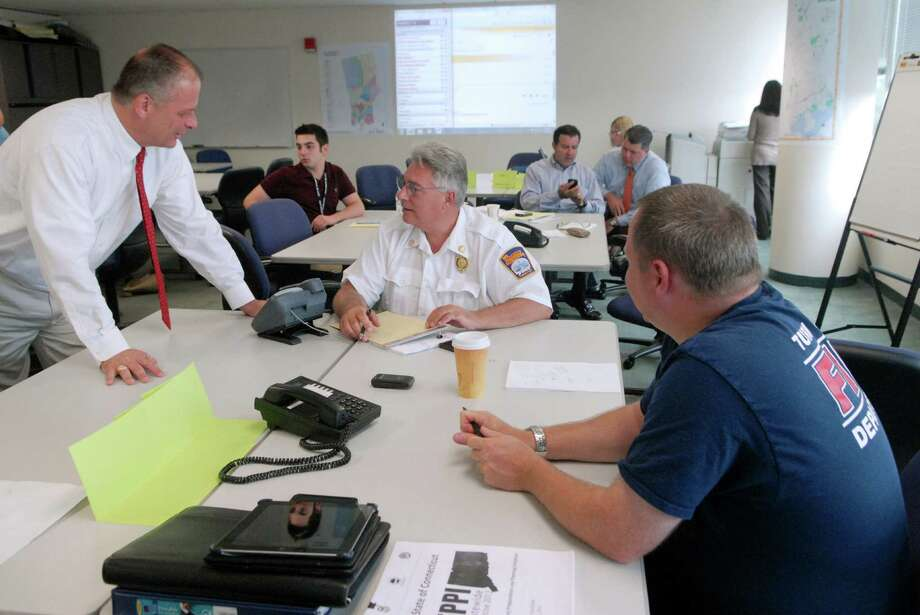 Ted Jankowsky, Public Safety Director, Stamford Fire and Rescue Chief Tony Conte and Lt Nicholas Jossem from Turn of River Fire Dept. are part of the group of emergency officials who gathered at the Government Center in Stamford, Conn. on  Monday July 30, 2012 to participate in a statewide drill to test and improve emergency coordination between public and private agencies in the event of a category three hurricane. Photo: Dru Nadler / Stamford Advocate Freelance