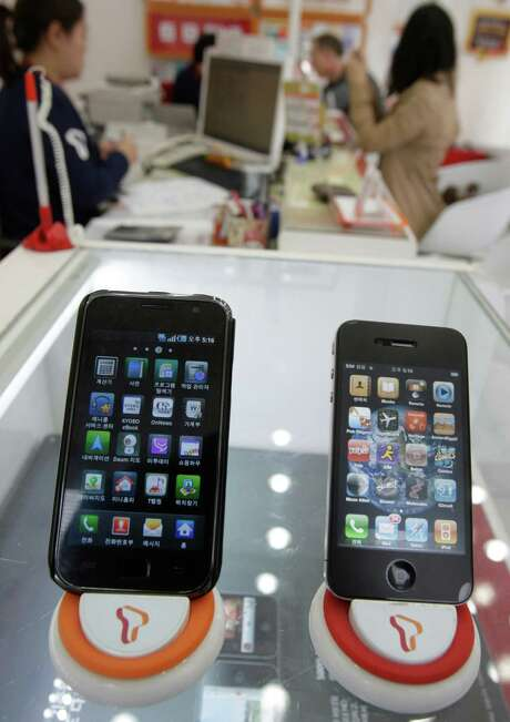 FILE - In this April 19, 2011 file photo, Samsung Electronics' Galaxy S, left, and Apple's iPhone 4 are displayed at a mobile phone shop in Seoul, South Korea. Two tech titans are squaring off in federal court Monday in a closely watched trial over control of the worldwide smart phone and computer tablet markets. Apple Inc. filed a lawsuit against Samsung Electronics Co. last year alleging the world's largest technology company's smart phones and computer tablets are illegal knockoffs. Samsung countered that it's Apple that is doing the stealing and, besides, some of the technology at issue such as the rounded rectangular designs of smart phones have been industry standards for years. Photo: AP