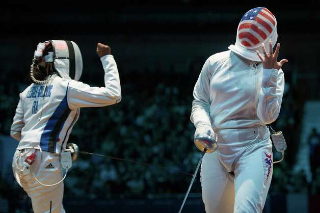 Courtney Hurley, right, reacts after losing a point against France's Laura Flessel-Colovic, left, in women's individual epee competition at the 2012 London Olympics on Monday, July 30, 2012. Hurley, of San Antonio, Texas, lost the opening round match 15-12. Photo: Smiley N. Pool, Houston Chronicle / © 2012  Houston Chronicle