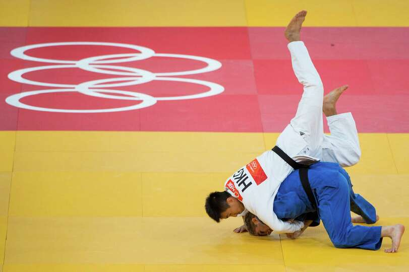 Nick Delpopolo of the USA, in blue, fights Chi Yip Cheung of Hong Kong in the men's judo 73kg class