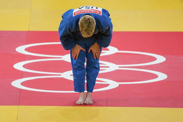 Nick Delpopolo of the USA, in blue, bows toward his opponent Chi Yip Cheung of Hong Kong after winning a men's judo 73kg class bout at the 2012 London Olympics on Monday, July 30, 2012. Delpopolo won the bout to advance to the round of 16. Photo: Smiley N. Pool, Houston Chronicle / © 2012  Houston Chronicle