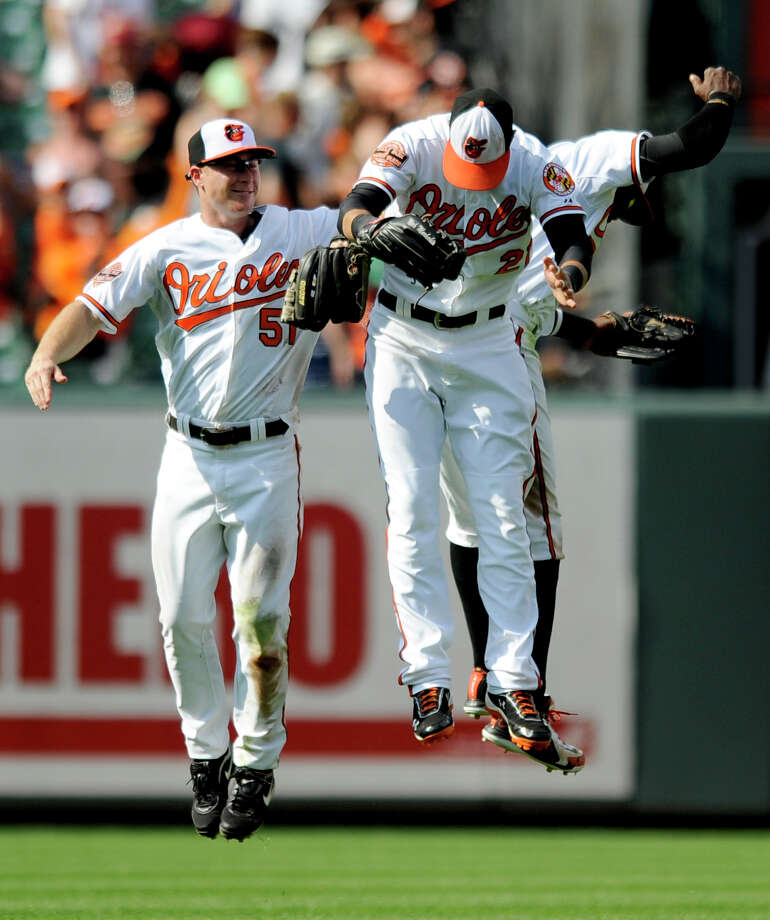 Baltimore Orioles right fielder Nick Markakis, center, Lew Ford (51) and Adam Jones, rear right, celebrate their 6-1 win over the Oakland Athletics in a baseball game, Sunday, July 29, 2012, in Baltimore. (AP Photo/Nick Wass) Photo: Nick Wass, FRE / FR67404 AP