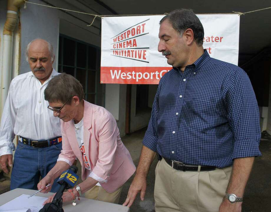 Westport Cinema Initiative Director Sandy Lefkowitz, center, signs an agreement in the parking lot of 142 Main St., which paves the way for the downtown lot to be developed into a new movie theater. At left, Philip Haemo de Thorneycroft Teuscher, one of 142 Main St.'s owners, and state Rep. Jonathan Steinberg, president of WCI's Board of Directors, look on. Photo: Paul Schott / Westport News
