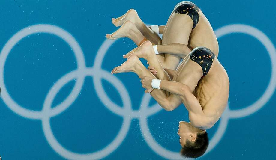 TOPSHOTS China's Cao Yuan and Zhang Yanquan compete in the men's synchronised 10m platform final diving event in the London 2012 Olympic Games at the Olympic Park on July 30, 2012.  China won gold. AFP PHOTO / LEON NEALLEON NEAL/AFP/GettyImages Photo: Leon Neal, AFP/Getty Images