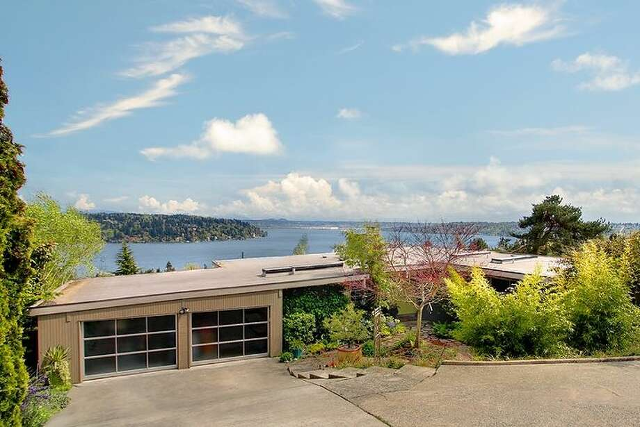 Want to live in mid-century modern style on Lake Washington? Check out this home, 6245 Chatham Drive S. The 3,118-square-foot home, built in 1958, has four bedrooms, three bathrooms, two-sided sandstone-clad fireplace, beamed ceilings, marble and granite floors, a wall of windows, a family room, two decks, gardens and a playground on one-third of an acre. It's listed for $1.08 million. Photo: Courtesy Mark Besta/Windermere Real Estate