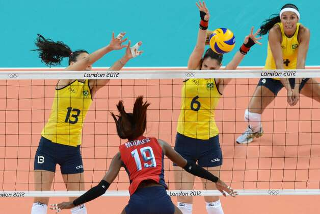 US' Destinee Hooker (C) spikes as Brazil's Sheilla Castro (L) and Thaisa Menezes (2R) attempt to block during the women's preliminary pool B volleyball match between USA and Brazil during the 2012 London Olympic Games in London on July 30, 2012. (KIRILL KUDRYAVTSEV / AFP/Getty Images)