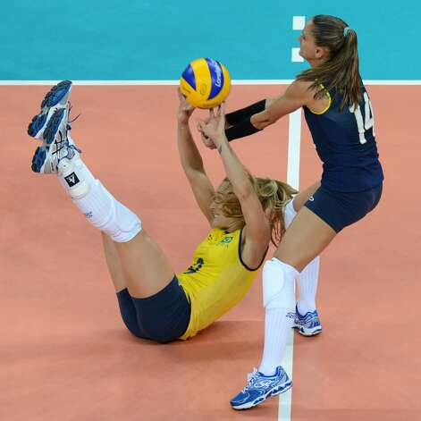 Brazil's Fernanda Ferreira (L) and Fabiana Oliveira attempt to set the ball during the women's preliminary pool B volleyball match between the US and Brazil in the 2012 London Olympic Games in London on July 30, 2012. (KIRILL KUDRYAVTSEV / AFP/Getty Images)