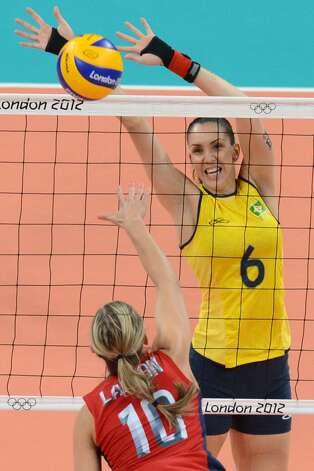 US player Jordan Larson spikes the ball as Brazil's Thaisa Menezes (top) attempts to block during the women's preliminary pool B volleyball match between the US and Brazil in the 2012 London Olympic Games in London on July 30, 2012. (KIRILL KUDRYAVTSEV / AFP/Getty Images)