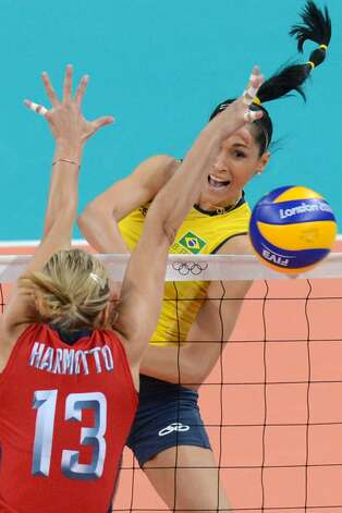 Brazil's Jaqueline Carvalho (R) spikes the ball as US player Christa Harmotto attempts to block during the women's preliminary pool B volleyball match between the US and Brazil in the 2012 London Olympic Games in London on July 30, 2012. (KIRILL KUDRYAVTSEV / AFP/Getty Images)