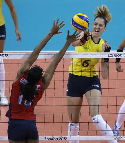 Brazil's Thaisa Menezes, right, spikes the ball past United States' Foluke Akinradewo during a women's preliminary volleyball match at the 2012 Summer Olympics, Monday, July 30, 2012, in London. (Jeff Roberson / Associated Press)