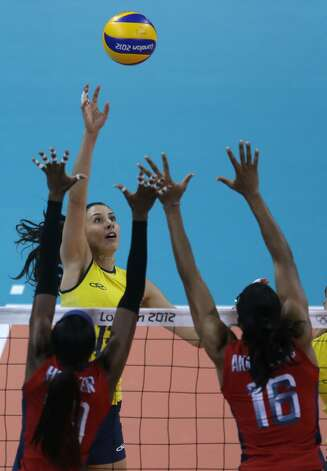 Brazil's Sheilla Castro returns the ball over United States' Destinee Hooker, left, and Foluke Akinradewo, right, during a women's preliminary volleyball match at the 2012 Summer Olympics, Monday, July 30, 2012, in London. (Jeff Roberson / Associated Press)