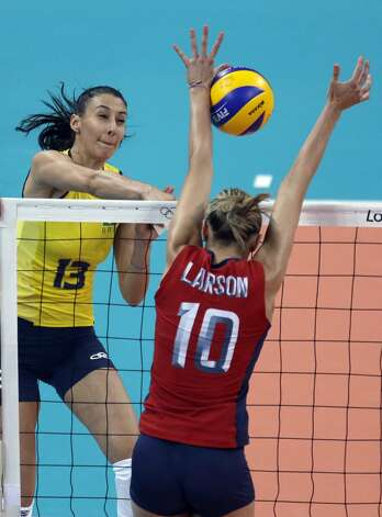 Brazil's Sheilla Castro, left, spikes the ball past United States' Jordan Larson during a women's preliminary volleyball match at the 2012 Summer Olympics, Monday, July 30, 2012, in London. (Jeff Roberson / Associated Press)