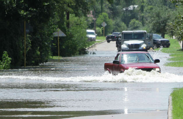 A truck drives past a Brinks' armored truck that was stalled in the Cypress Creek floodwaters along Grant Road near Oak Hollow Saturday, July 14, 2012, in Cypress. ( Melissa Phillip / Houston Chronicle ) Photo: Melissa Phillip, Staff / © 2012 Houston Chronicle