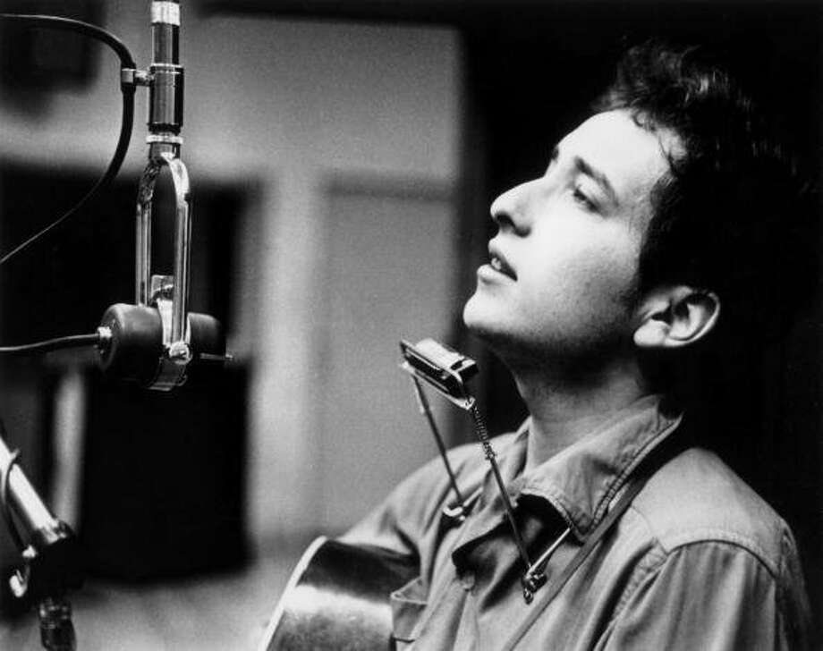 Profile headshot of American musician and vocalist Bob Dylan seated in front of a microphone with a guitar and a harmonica during one of the John Hammond recording sessions for Dylan's first album. These sessions took place between November 1961 and March 1962 at Columbia Studio, New York City.  (Frank Driggs  / Getty Images)