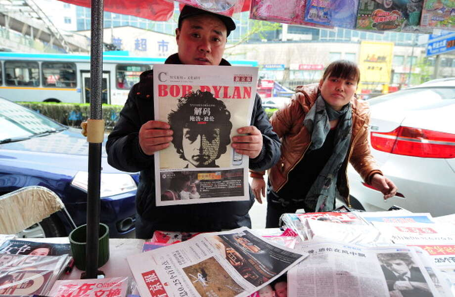 "A news stand vendor displays the Entertainment and Culture section of a Beijing newspaper with a image of Bob Dylan on the cover on April 6, 2011 in Beijing. Dylan was kicking off a series of first-ever shows in China marking his 50th year as one of the world's most influential performing artists. China's media gave Dylan's first-ever China performances wide coverage with the current edition of the influential Lifeweek magazine doing a cover story on the singer entitled ""The Answer Is Still Blowing in the Wind."" (FREDERIC J. BROWN / AFP/Getty Images)"
