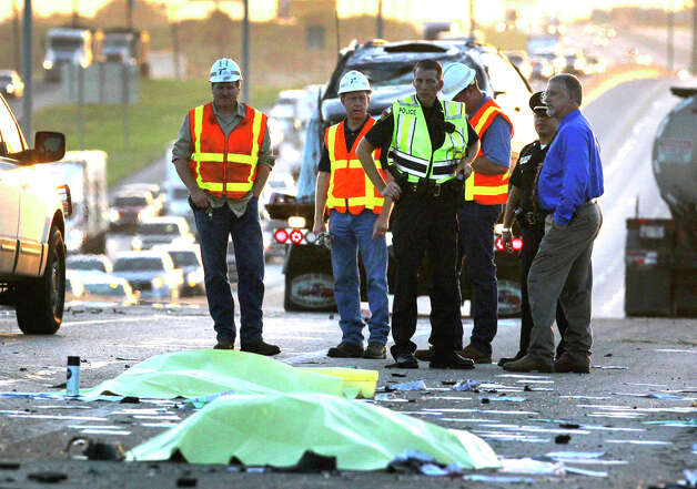 Police and others work at the scene of a triple fatality traffic accident Monday morning after a wrong way driver in a Toyota Camry slammed into a Dodge Durango carrying a family of five on IH-35 near FM 1103, according to City of Schertz spokesman Brad Bailey. Bailey said an attendant at a rest stop and a bus driver attempted to rescue people trapped in the Durango when they were struck by a passing truck killing both of them and the driver of the Toyota Camry. The accident took place in the northbound lanes of I-35 shortly after 3:00 a.m. Photo: John Davenport/© San Antonio Ex, San Antonio Express-News / John Davenport/©San Antonio Exp