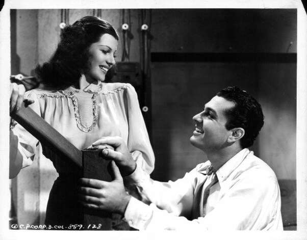 Rita Hayworth and Tony Martin hold hands at foot of stairs in a scene from the film 'Music In My Heart', 1940.  (Columbia Pictures / Getty Images)