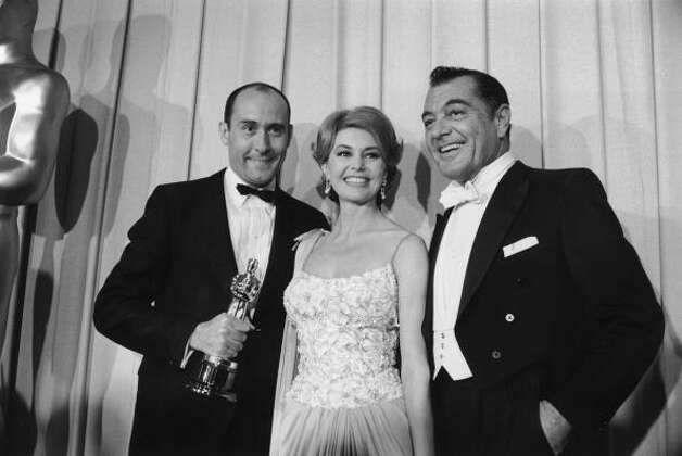 L-R: American composer Henry Mancini, American dancer Cyd Charisse, and American actor Tony Martin pose backstage at the Academy Awards on April 9, 162 in Santa Monica, California. Mancini won his Oscar for Best Musical Score, which he received for his work on director Blake Edwards' film, 'Breakfast at Tiffany's.'  (Gene Lester / Getty Images)