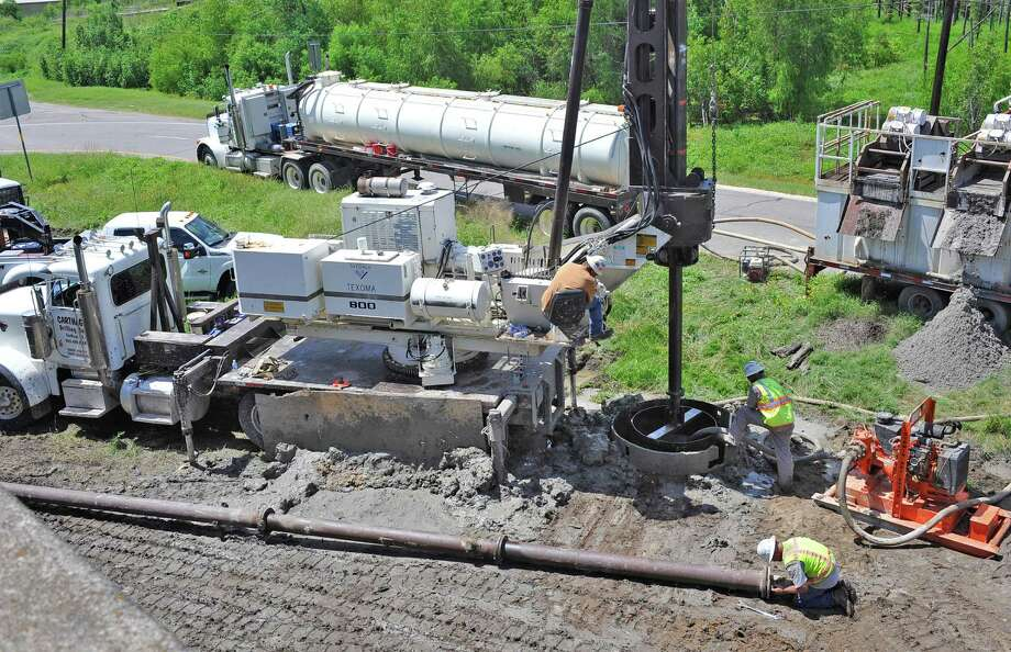 Brent Fehner, top left, was manning the giant drill as the first of 6, 150-175 foot high mast light support holes was being drilled down to 47 feet. Carthage Drilling, Inc., the contractor for the high mast lighting on the Neches River Bridge started installation Monday July 30, 2012 by drilling the first hole for the support stand. This is the first step in the major project to complete the construction of the new  bridge over the Neches River. Dave Ryan/The Enterprise Photo: Dave Ryan