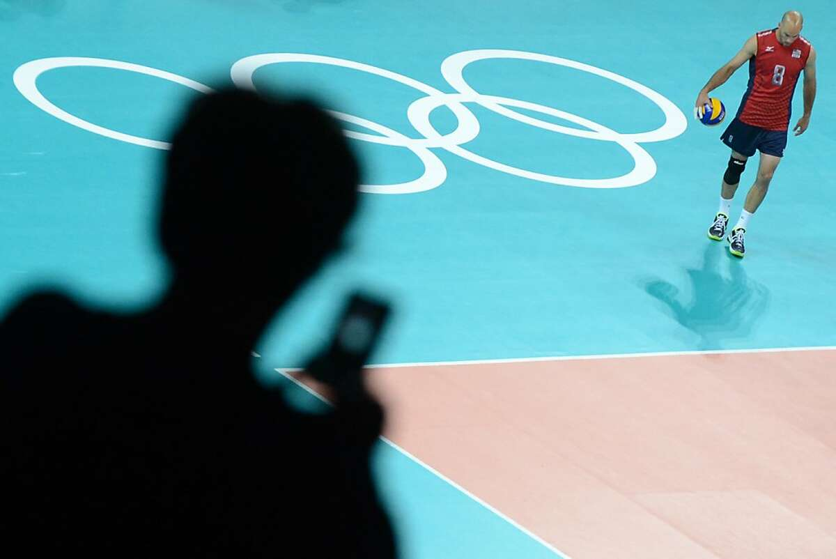 A visitor takes a picture with a mobile phone of US' William Priddy before the men's volleyball match between USA and Serbia in the 2012 London Olympic Games in London on July 29, 2012. AFP PHOTO / KIRILL KUDRYAVTSEVKIRILL KUDRYAVTSEV/AFP/GettyImages