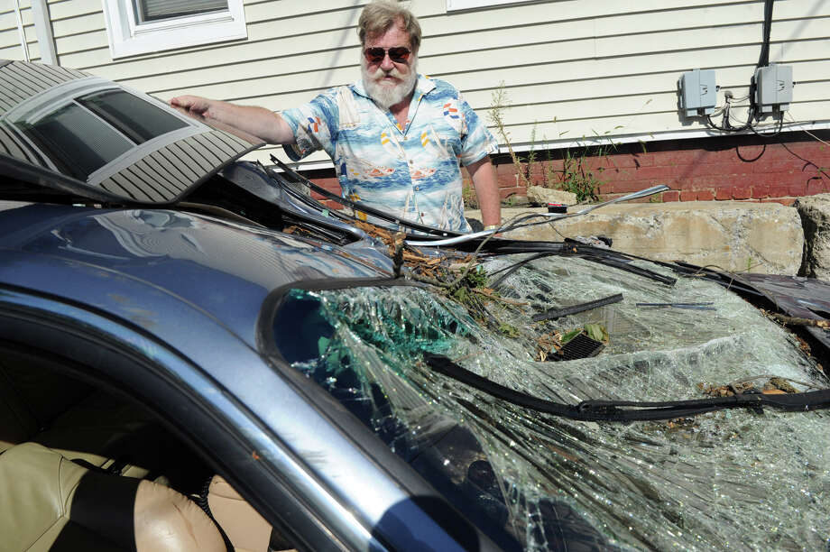 Gerhard Hutter adjusts the warped sun roof of his totaled 2001 BMW in Stamford, Conn., July 30, 2012.  Hutter was driving on Long Ridge Road when a tree fell on his car Sunday morning. Photo: Keelin Daly / Stamford Advocate