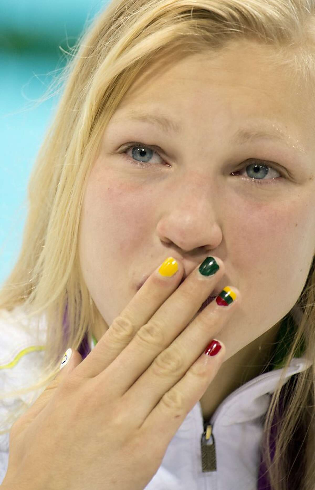 Ruta Meilutyte of Lithuania with her national flag painted on her nails blows a kiss to the crowd at the Aquatics centre after winning the women's 100m breaststroke of the 2012 Olympic Games in London on July 30, 2012. AFP PHOTO / ODD ANDERSENODD ANDERSEN/AFP/GettyImages