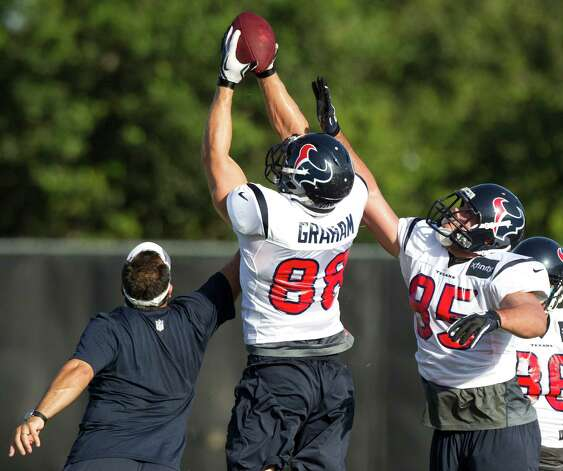 Houston Texans tight ends coach Brian Pariani, left, goes up for a ball with tight ends Garrett Graham (88) and Logan Brock (85) during at turnover drill at Texans training camp at the Methodist Training Center Monday, July 30, 2012, in Houston.  ( Brett Coomer / Houston Chronicle ) Photo: Brett Coomer, Staff / © 2012 Houston Chronicle