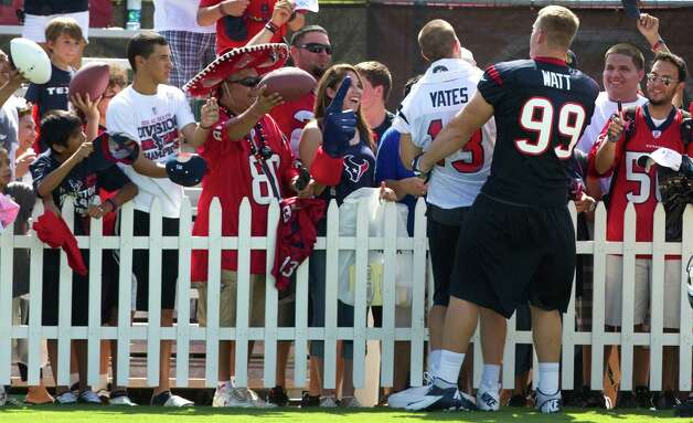 Houston Texans fans lines a fence waiting for quarterback T.J. Yates (13) and defensive end J.J. Watt (99) to sign autographs following practice at Texans training camp at the Methodist Training Center Sunday, July 29, 2012, in Houston.  ( Brett Coomer / Houston Chronicle ) Photo: Brett Coomer, Staff / © 2012 Houston Chronicle