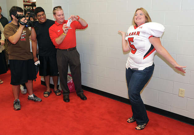 Wearing a Lamar jersey and pads, Adrianna Champagne shows off for the cameras during a special class Monday where Lamar coaches taught several women the fundamentals of football. Photo taken Monday, July 30, 2012  Guiseppe Barranco/The Enterprise Photo: Guiseppe Barranco, STAFF PHOTOGRAPHER / The Beaumont Enterprise