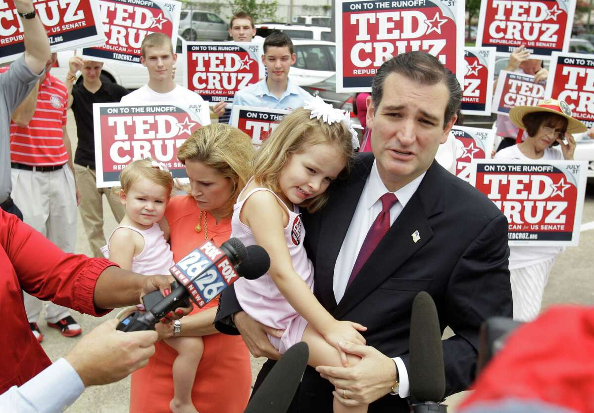 Ted Cruz, Republican candidate for U.S. Senate, holds his daughter, Caroline, 4, as his wife, Heidi Cruz holds their daughter, Catherine, 1, while he speaks to the media before voting during the first day of early voting at the Metropolitan Multi-Service Center, in Houston, Monday, July 23, 2012.