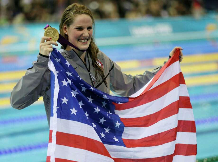 United States' Missy Franklin poses for photographers with her gold medal for the women's 100-meter backstroke swimming final at the Aquatics Centre in the Olympic Park during the 2012 Summer Olympics in London, Monday, July 30, 2012. Photo: AP