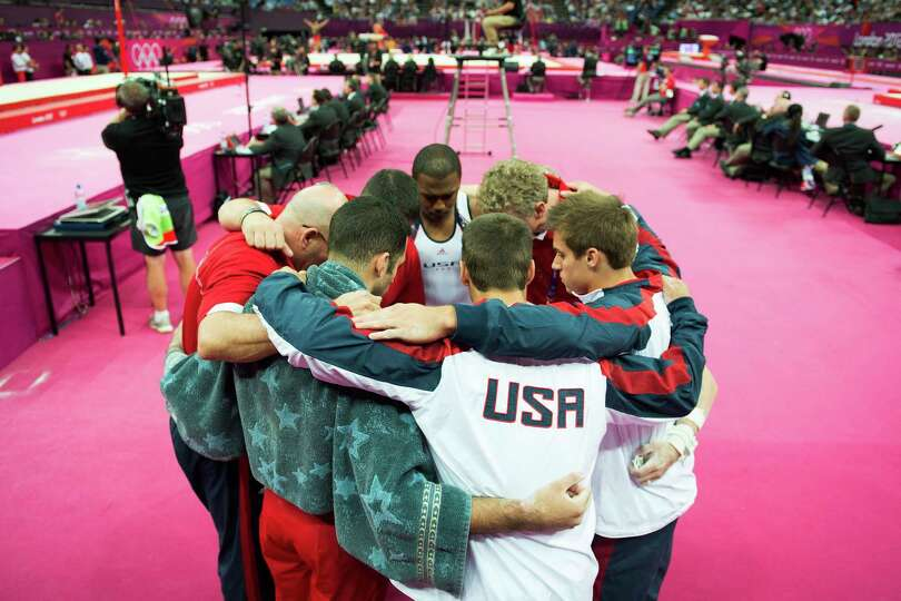 Team USA huddles before performing on the horizontal bar, their final apparatus of the competition,