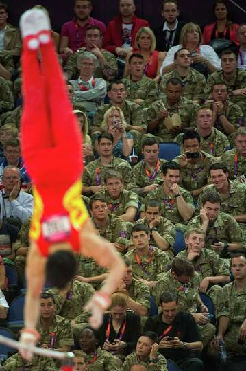 A group of soldiers watches as Zou Kai of China performs on the horizontal bar during the men's gymn
