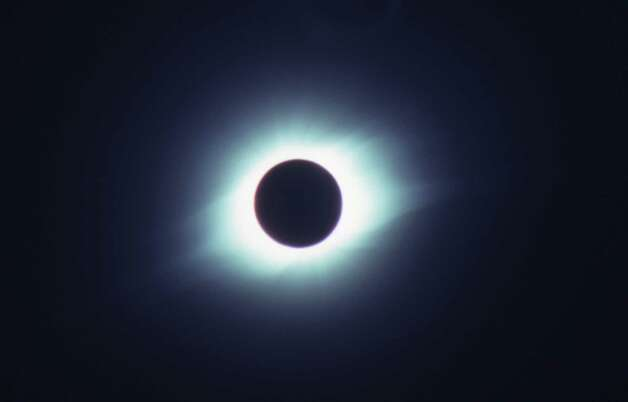 This moment of totality – when the moon completely covers the sun – is why eclipse-chasers travel thousands of miles (in this case going to the island of Curacao in the Caribbean Sea in 1998) to see them.  Although totality only lasts a few minutes, eclipsophiles say it's well worth the money and effort. (© April Orcutt – all rights reserved) Photo: April Orcutt, For The Express-News / © April Orcutt.  All rights reserved.