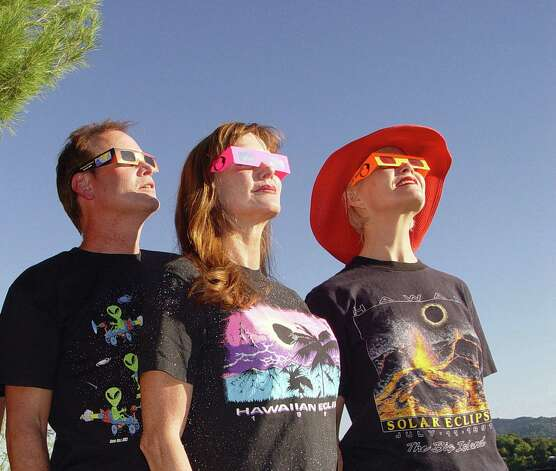 Nick Johnson, Diane Waye and Marty Lucas (left to right) try out eclipse glasses and souvenir T-shirts from previous eclipses in San Anselmo, Calif., in preparation for the next total solar eclipse in Australia on Nov. 14, 2012. (© April Orcutt – all rights reserved) Photo: April Orcutt, For The Express-News / © April Orcutt.  All rights reserved.