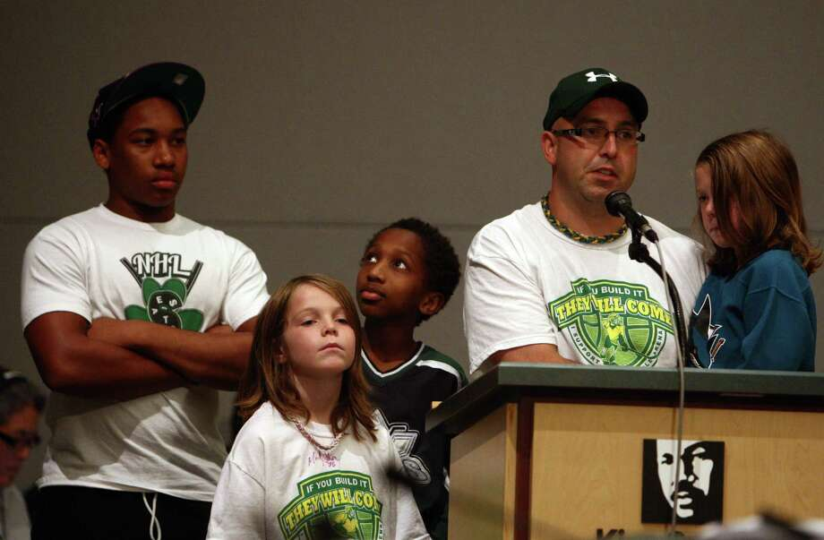 Todd Smith, owner of Bruised Ego Sports, stands at the podium with four of his six kids as he talks about how a new sports team would strengthen his business during a meeting of the King County Council on Monday, July 30, 2012 at Metropolitan King County Council chambers. Photo: JOSHUA TRUJILLO / SEATTLEPI.COM