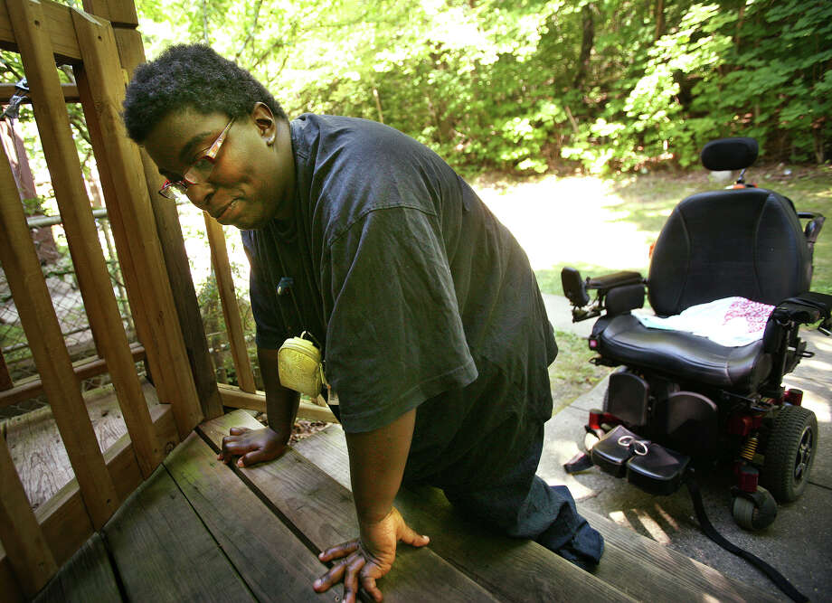 Tosha Newton, 31, who has had cerebral palsy since birth, is forced to crawl up the stairs of her home 270 Texas Avenue in Bridgeport on Monday, July 30, 2012. Newton is hoping to have a ramp built so that she can drive her motorized wheelchair into the house. Photo: Brian A. Pounds / Connecticut Post