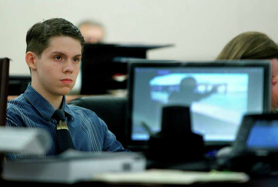 Alex Olivieri, 19, looks at a video of himself at a shooting range shown during his murder trial on Monday. Photo: Mayra Beltran / © 2012 Houston Chronicle
