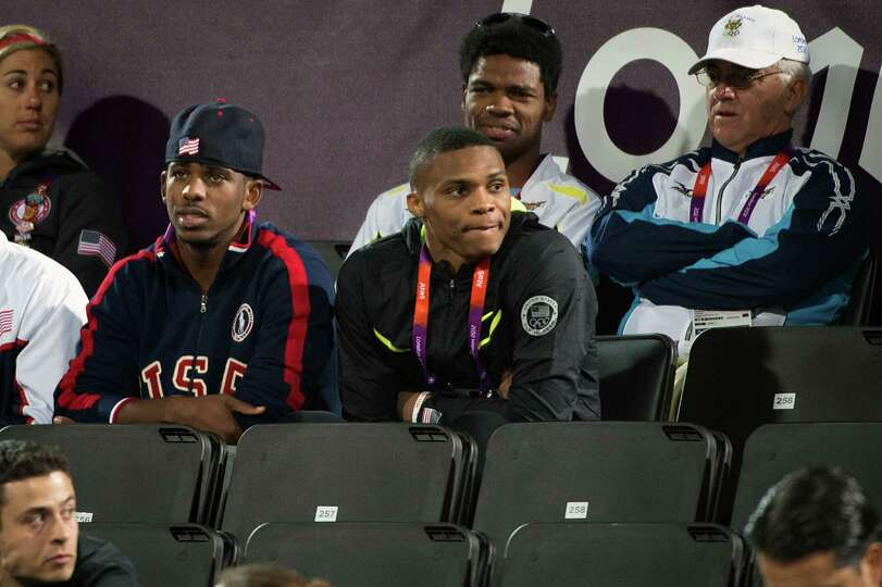USA basketball players Chris Paul, left, and Russell Westbrook watch a beach volleyball game at the