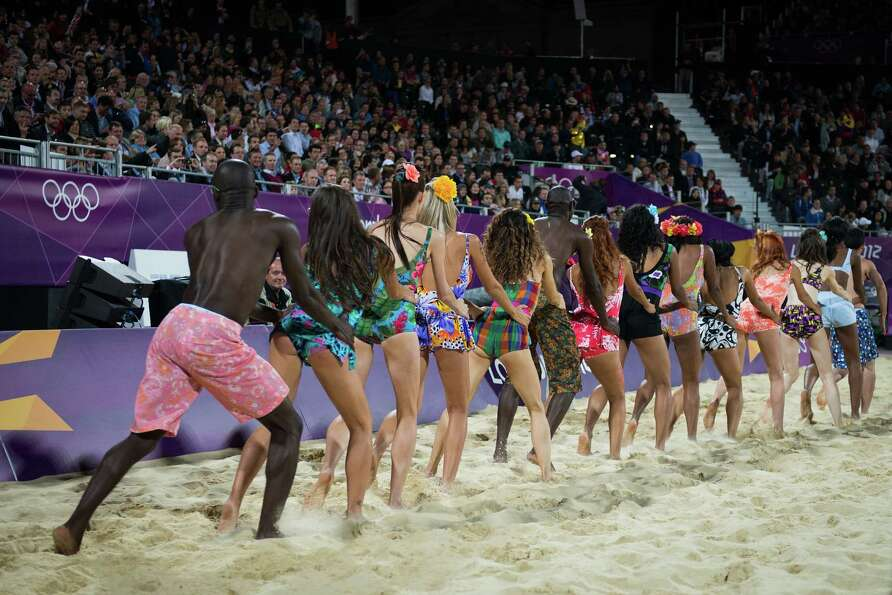 A dance team forms a conga line during a timeout of a beach volleyball match at the 2012 London Olym