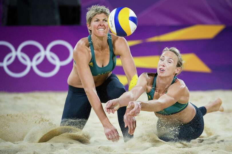 Tamsin Hinchley, right, and Natalie Cook of dive for a ball during a beach volleyball match against