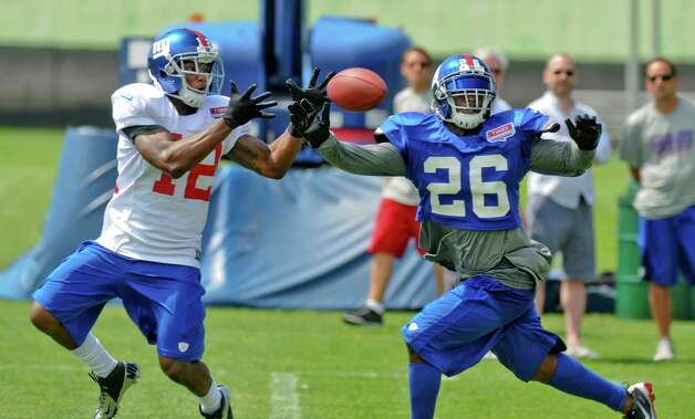 New York Giants wide receiver Jerrel Jernigan catches a pass in front of safety Antrel Rolle during a training camp practice at UAlbany on Monday July 30, 2012 in Albany, NY.   (Philip Kamrass / Times Union) Photo: Philip Kamrass / 00018618A
